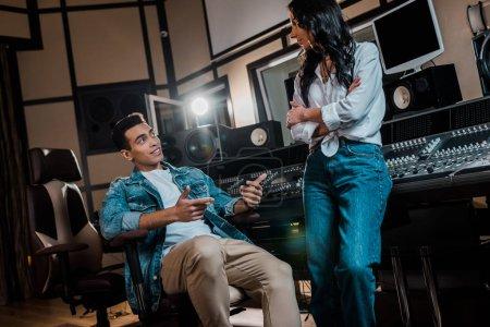 Photo pour Deux jeunes producteurs sonores multiculturels parlent près de la console de mixage en studio d'enregistrement - image libre de droit