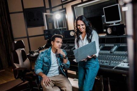 Photo pour Souriant joli producteur sonore à l'aide d'un ordinateur portable près d'un ami mixte en studio d'enregistrement - image libre de droit