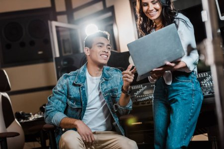 Photo for Smiling multicultural sound producers using laptop in recording studio - Royalty Free Image