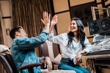 Photo pour Deux producteurs sonores multiculturels joyeux donnant cinq dans le studio d'enregistrement - image libre de droit
