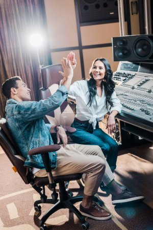 Photo for Two cheerful multicultural sound producers giving five in recording studio while sitting near mixing console - Royalty Free Image