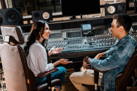 Photo for Two smiling multicultural sound producers sitting by mixing console in recording studio - Royalty Free Image