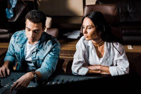 Photo pour Deux producteurs sonores multiculturels concentrés travaillant à la console de mixage en studio d'enregistrement - image libre de droit