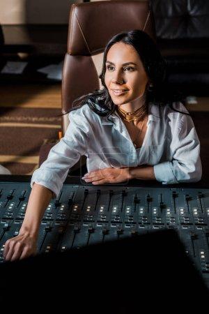 Photo pour Beau producteur sonore souriant travaillant à la console de mixage en studio d'enregistrement - image libre de droit