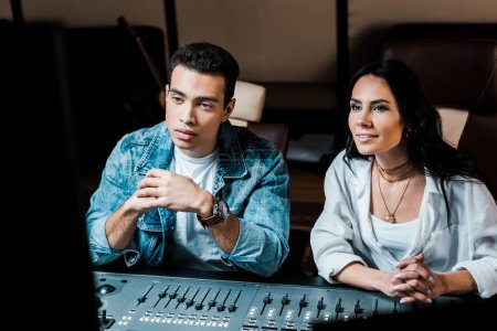 Photo for Two attentive multicultural sound producers working at mixing console in recording studio - Royalty Free Image