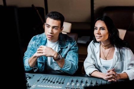 Foto de Two attentive multicultural sound producers working at mixing console in recording studio - Imagen libre de derechos