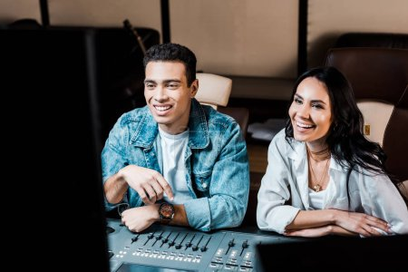 Photo for Two cheerful multicultural sound producers working at mixing console in recording studio - Royalty Free Image