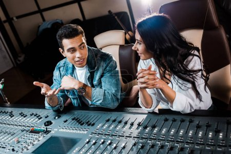 Photo for Two smiling multicultural sound producers talking while sitting near mixing console in recording studio - Royalty Free Image