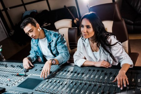 Photo for Two young attentive multicultural sound producers working at mixing console in recording studio - Royalty Free Image