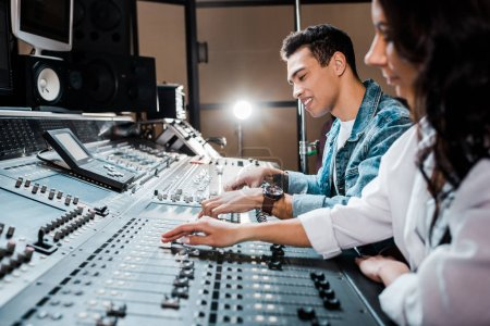 Photo for Two young multicultural sound producers working at mixing console i recording studio - Royalty Free Image