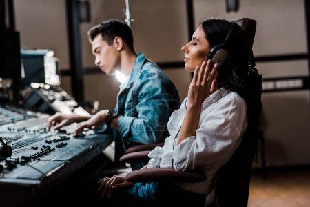 Photo pour Producteur de son assez dans les écouteurs écouter de la musique près d'ami raciale mixte travaillant à la console de mixage - image libre de droit