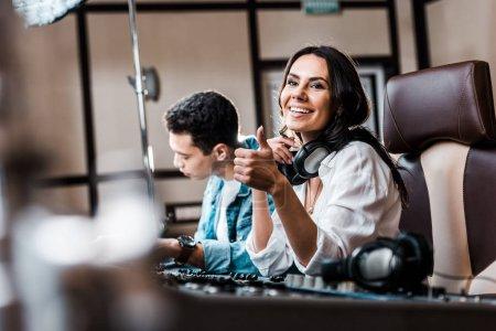 Photo pour Mise au point sélective du son souriant produire montrant pouce vers le haut tout en travaillant à la console de mélange près ami de course mixte - image libre de droit