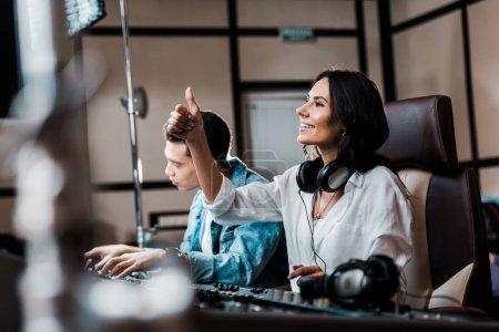 Photo pour Mise au point sélective de producteur assez sonore dans les écouteurs de travail à la console de mixage près ami de course mixte - image libre de droit