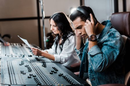 Photo for Selective focus of handsome mixed race sound producer in earphones near pretty colleague working at mixing console - Royalty Free Image