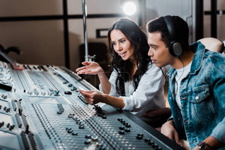 Photo for Two young multicultural sound producers working at mixing console in recording studio - Royalty Free Image