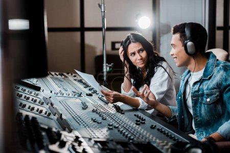 Photo pour Deux producteurs de sons parlent tout en travaillant à la console de mixage en studio d'enregistrement - image libre de droit