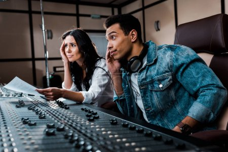 Photo for Two thoughtful sound producers working at mixing console in recording studio - Royalty Free Image