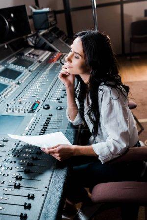 Photo pour Beau producteur sonore rêveur travaillant en studio d'enregistrement à la console de mixage - image libre de droit
