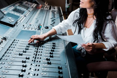 cropped view of sound producer working in recording studio at mixing console