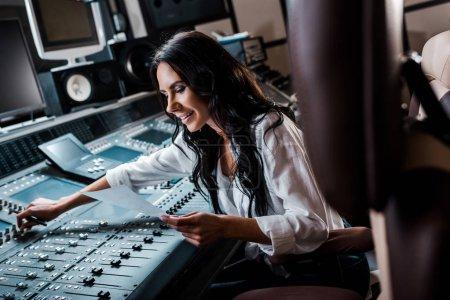 Photo pour Producteur sonore de sourire attrayant travaillant à la console de mélange dans le studio d'enregistrement - image libre de droit