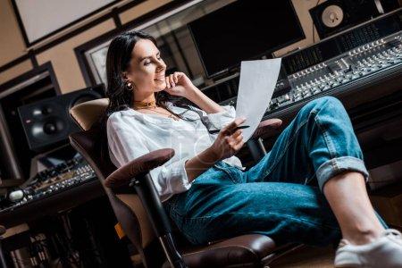 Photo pour Beau producteur de son de sourire s'asseyant dans la présidence de bureau près de la console de mélange dans le studio d'enregistrement - image libre de droit