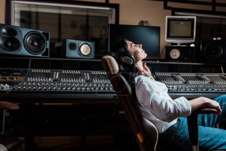 Photo for Pretty sound producer listening music in headphones while sitting in office chair in recording studio - Royalty Free Image