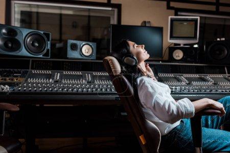 hübscher Soundproduzent, der Musik im Kopfhörer hört, während er im Bürostuhl im Tonstudio sitzt