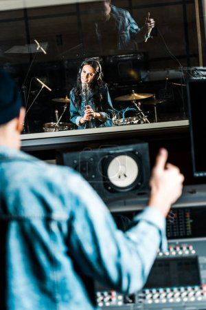 selective focus of mixed race sound producer showing thumb up to beautiful singing girl