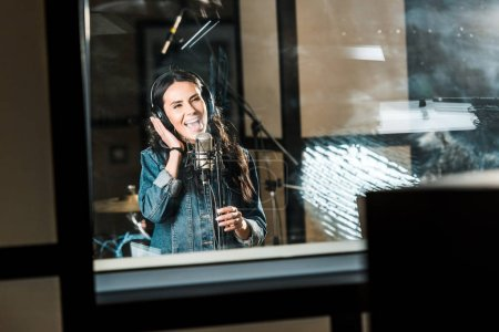 Photo pour Beautiful, inspired musician singing near microphone in recording studio - image libre de droit