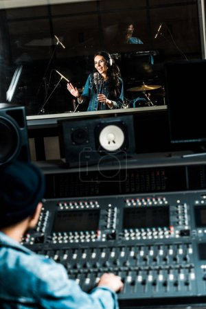Photo pour Selective focus of mixed race sound producer working at mixing console while pretty woman singing in recording studio - image libre de droit