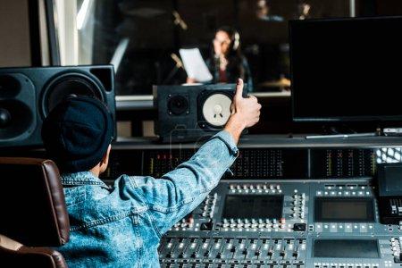 Photo pour Mise au point sélective de la race mixte producteur sonore montrant pouce vers le haut à la femme chantant dans le studio d'enregistrement - image libre de droit