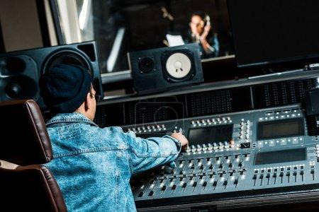 Photo pour Mise au point sélective de la race mixte producteur sonore de travail à la console de mixage tout en jolie femme chantant en studio d'enregistrement - image libre de droit