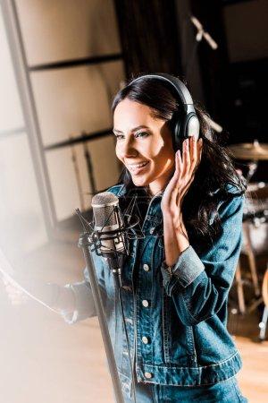 Photo pour Selective focus of inspired woman in headphones singing in recording studio - image libre de droit