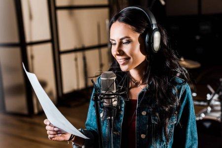 Photo pour Pretty woman in headphones singing in recording studio near microphone - image libre de droit