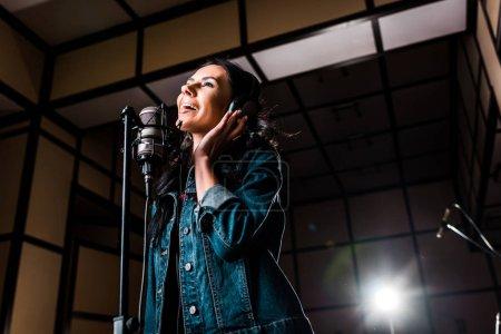Photo pour Belle femme inspirée chantant près du microphone dans le studio d'enregistrement sombre - image libre de droit