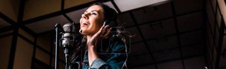 Photo pour Tir panoramique de belle femme inspirée chantant près du microphone dans le studio d'enregistrement - image libre de droit