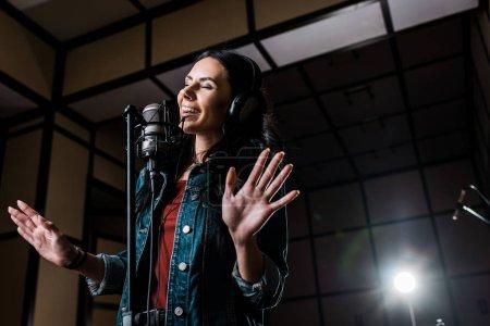 Photo pour Femme inspirée attirante chantant près du microphone dans le studio d'enregistrement - image libre de droit