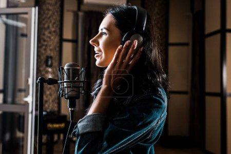 Photo pour Vue latérale de la belle femme chantant près du microphone dans le studio d'enregistrement - image libre de droit