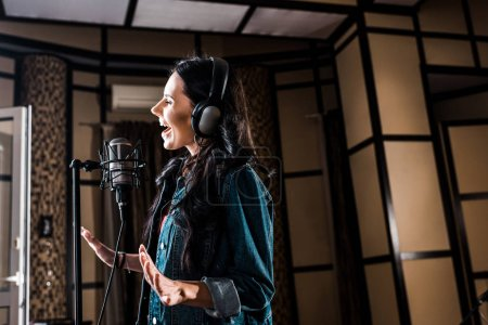 Photo for Beautiful inspired woman singing near microphone in recording studio - Royalty Free Image