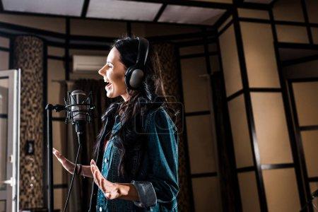 Photo pour Belle femme inspirée chantant près du microphone dans le studio d'enregistrement - image libre de droit