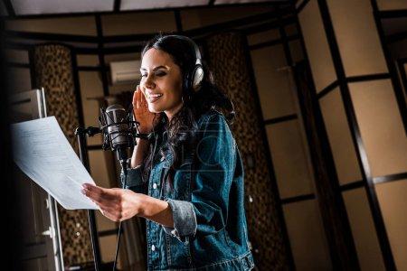Photo pour Foyer sélectif du papier attirant de fixation de femme avec le texte et chantant dans le studio d'enregistrement - image libre de droit
