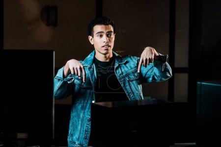 Photo pour Beau producteur de son de race mixte faisant des gestes dans le studio d'enregistrement sombre - image libre de droit
