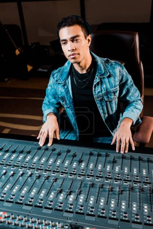 Photo for Concentrated mixed race sound producer working at mixing console in recording studio - Royalty Free Image