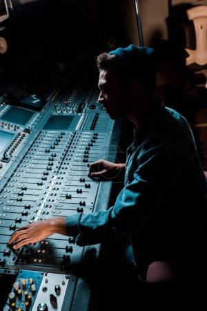 Photo pour Producteur de son travaillant à la console de mixage dans le studio d'enregistrement foncé - image libre de droit