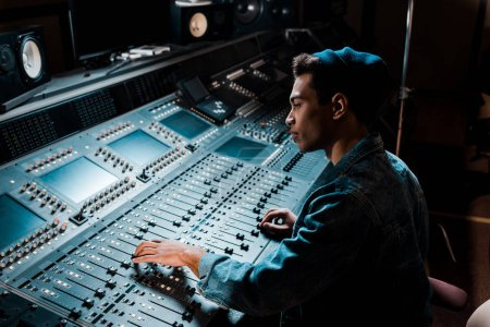 concentrated mixed race sound producer working at mixing console in dark recording studio