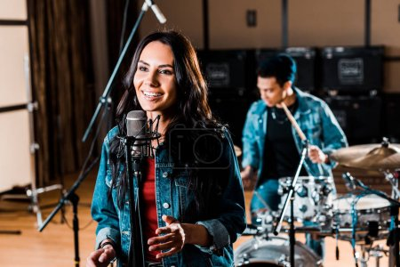 Photo pour Pretty woman singing while mixed race musician playing drums in recording studio - image libre de droit