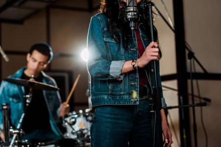 selective focus of woman singing in recording studio while mixed race musician playing drums