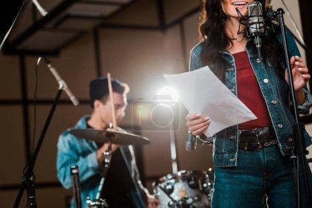 Photo pour Vue partielle de femme de sourire chantant dans le studio d'enregistrement tandis que le musicien mélangé de course jouant la batterie - image libre de droit