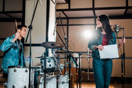 Photo pour Handsome mixed race musician at drums and attractive singer near microphone in recording studio - image libre de droit