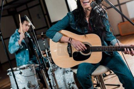 Photo pour Vue partielle du musicien jouant la guitare et chantant tandis que l'homme mélangé de course jouant la batterie dans le studio d'enregistrement - image libre de droit